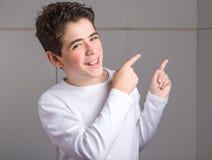 el señalar doble Liso-pelado del muchacho caucásico hasta su izquierda con Imagenes de archivo