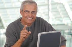 El señalar envejecido medio de la computadora portátil del hombre Imagenes de archivo