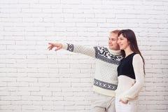 El señalar feliz de los pares sideway al espacio vacío de la copia Foto de archivo libre de regalías