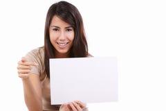 El señalar femenino joven a la tarjeta en blanco Foto de archivo