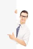 El señalar sonriente de los jóvenes en un panel Imagenes de archivo