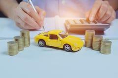 El seguro de coche con las monedas y el coche mantiene concepto Negocios imagenes de archivo
