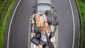 El selfie del hombre en el tejado del coche corría en el camino almacen de metraje de vídeo