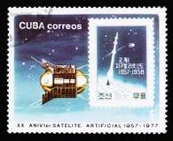El sello cubano muestra el satélite en el espacio, vigésimo aniversario de los años de la investigación del espacio, circa 1977 Fotos de archivo libres de regalías
