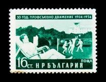 El sello de Bulgaria muestra al hombre en la silla, jugadores de voleibol, los sindicatos 50 años de aniversario, circa 1954 Fotos de archivo