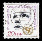 El sello impreso por RDA muestra la cabeza de Childs y el emblema de la Unicef Foto de archivo libre de regalías