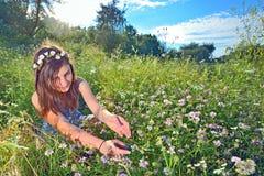 El sentarse adolescente al aire libre en un campo Imagen de archivo libre de regalías