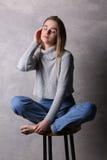 El sentarse adolescente en el jersey que toca su cara Fondo gris Imágenes de archivo libres de regalías