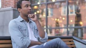 El sentarse africano de pensamiento del hombre al aire libre almacen de metraje de vídeo