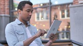 El sentarse africano del hombre al aire libre y usar la tableta almacen de video