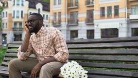 El sentarse africano triste del hombre solo en banco de la ciudad con el ramo de la flor, fallado fecha metrajes