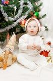 El sentarse bajo el árbol de navidad Fotografía de archivo libre de regalías