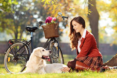 El sentarse bastante femenino con su perro en parque Imagenes de archivo