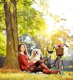 El sentarse bastante femenino con su perro en un parque Imagen de archivo