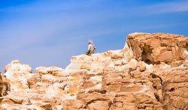 El sentarse beduino en el pico de una alta roca de piedra contra un cielo azul en Egipto Dahab Sina? del sur fotografía de archivo