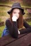 El sentarse bonito del adolescente al aire libre en una mesa de picnic Imágenes de archivo libres de regalías