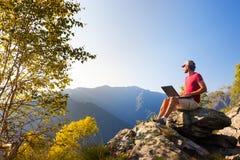 El sentarse caucásico joven del hombre al aire libre en una roca que trabaja en un lapto Fotografía de archivo