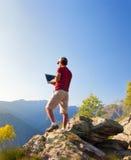 El sentarse caucásico joven del hombre al aire libre en una roca que trabaja en un lapto Imagen de archivo libre de regalías