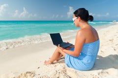 El sentarse con la computadora portátil en el mar Imagen de archivo