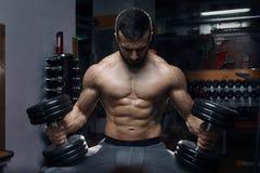 El sentarse con las tetas al aire muscular del hombre con las tetas al aire con pesas de gimnasia en el gimnasio Fotos de archivo libres de regalías