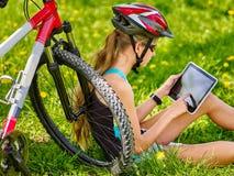 El sentarse de ciclo del casco de la muchacha que lleva cerca de la tableta de la PC del reloj de la bicicleta Fotos de archivo libres de regalías
