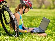 El sentarse de ciclo del casco de la muchacha que lleva que monta en bicicleta cerca del ordenador portátil del reloj de la bicic Imagen de archivo libre de regalías