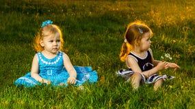 El sentarse de dos hermanas de las muchachas Imágenes de archivo libres de regalías