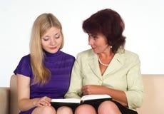 El sentarse de dos mujeres Imágenes de archivo libres de regalías