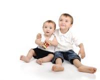 El sentarse de dos pequeños hermanos Foto de archivo
