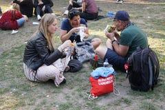 El sentarse de la consumición de la gente en hierba en parque Fotografía de archivo