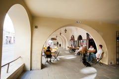 El sentarse de la gente al aire libre alrededor de las tablas de barra debajo de arcos Imagenes de archivo