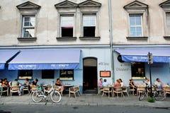 El sentarse de la gente joven al aire libre alrededor de las tablas de restaurante en ciudad vieja Foto de archivo