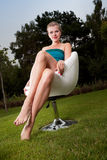 El sentarse de la muchacha al aire libre en una silla de eslabón giratorio Foto de archivo libre de regalías