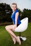 El sentarse de la muchacha al aire libre en una silla de eslabón giratorio Fotos de archivo