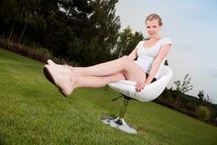 El sentarse de la muchacha al aire libre en una silla de eslabón giratorio Imagen de archivo