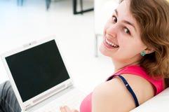 El sentarse de la mujer cómodo con la computadora portátil en el sofá Imagen de archivo libre de regalías
