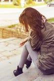 El sentarse de la mujer solo Foto de archivo libre de regalías