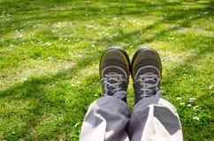 El sentarse de las piernas estirado en naturaleza Foto de archivo