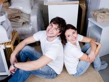 El sentarse de los pares adosado mutuamente después de mover Foto de archivo libre de regalías