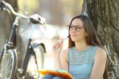 El sentarse de pensamiento del estudiante en un parque Fotos de archivo