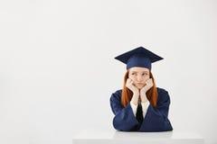 El sentarse de pensamiento graduado agujereado de la hembra cansada sobre el backround blanco Copie el espacio Imagenes de archivo