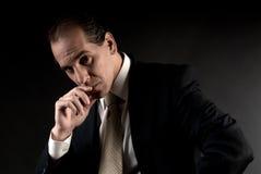 El sentarse de pensamiento serio del hombre de negocios adulto Imagen de archivo