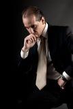 El sentarse de pensamiento serio del hombre de negocios adulto en obscuridad Imagenes de archivo