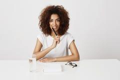 El sentarse de pensamiento sonriente de la muchacha africana hermosa en la tabla sobre el fondo blanco Copie el espacio Fotos de archivo libres de regalías