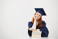 El sentarse de pensamiento sonriente de la muchacha graduada soñadora con los libros Copie el espacio Foto de archivo libre de regalías