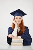 El sentarse de pensamiento sonriente de la muchacha graduada soñadora con los libros sobre el fondo blanco Fotografía de archivo libre de regalías