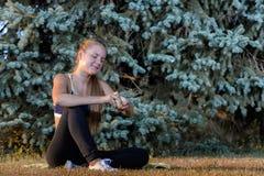 El sentarse de reclinación de la chica joven en la hierba Fotos de archivo libres de regalías