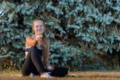 El sentarse de reclinación de la chica joven en la hierba Imágenes de archivo libres de regalías