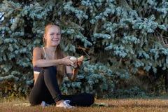El sentarse de reclinación de la chica joven en la hierba Fotos de archivo