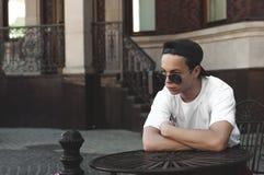 El sentarse de reclinación del hombre joven en una tabla en una calle de la ciudad Fotografía de archivo libre de regalías
